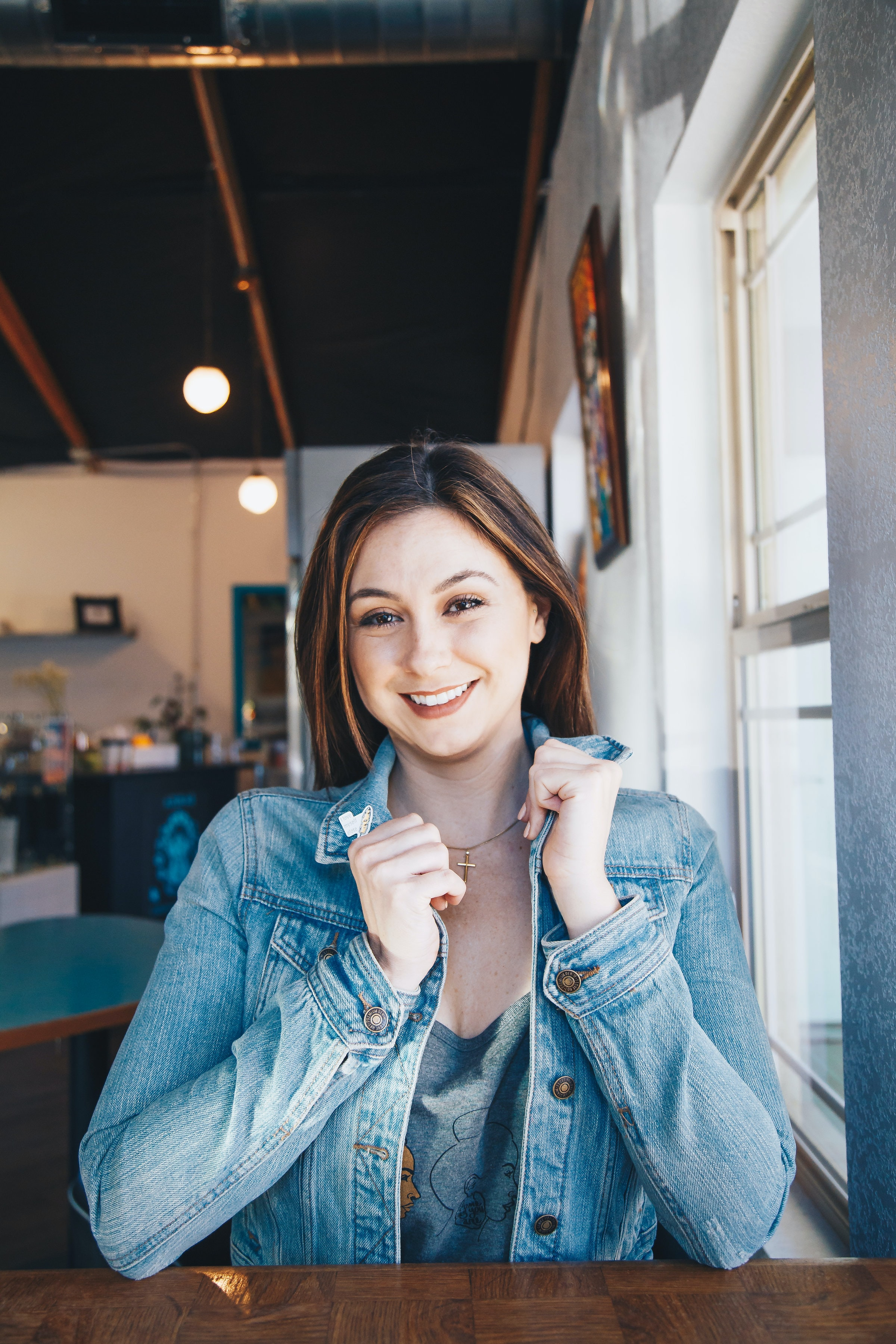 smiling woman wearing blue denim jacket holding her collar leaning on table beside clear glass window