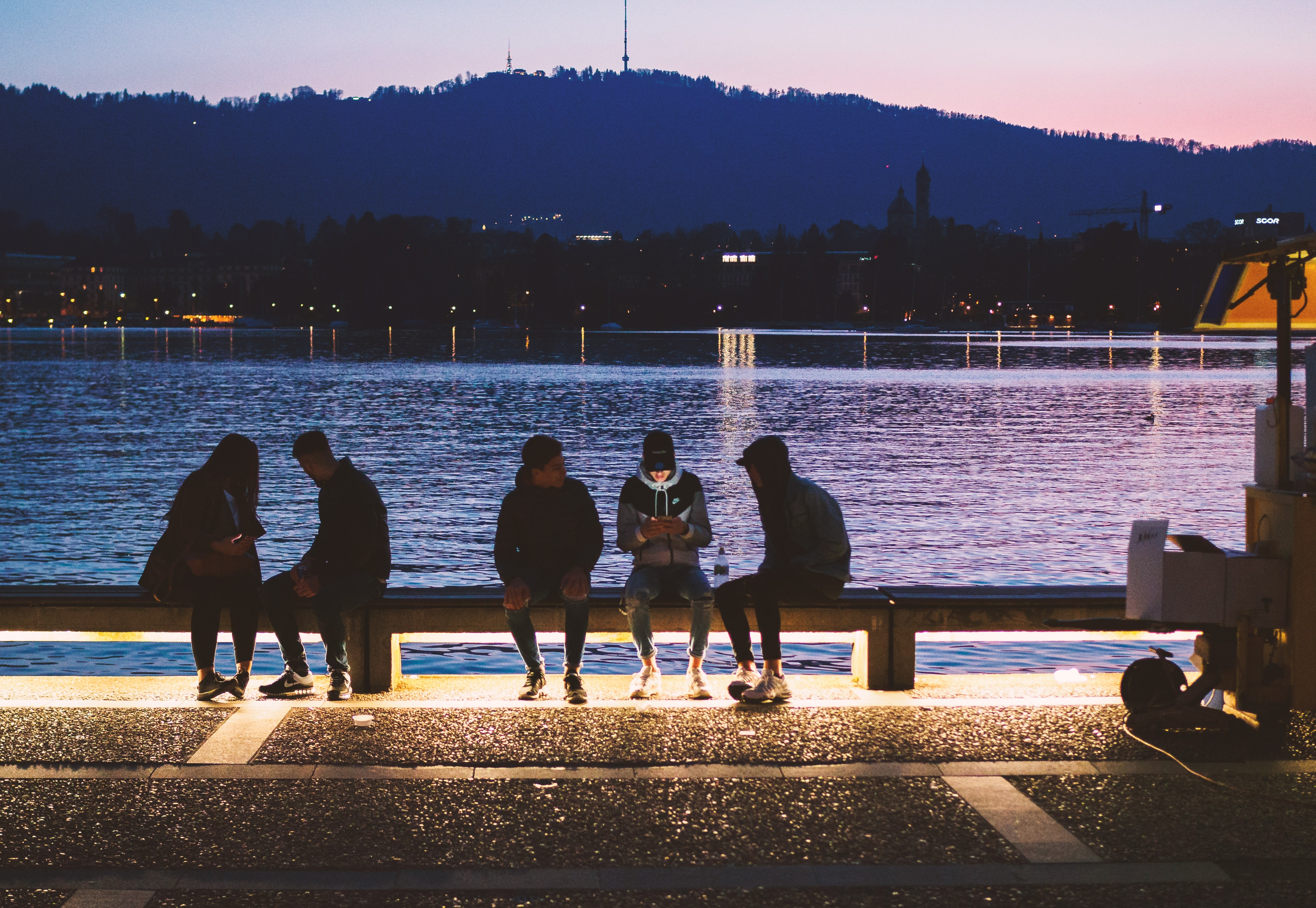 five people sitting near body of water