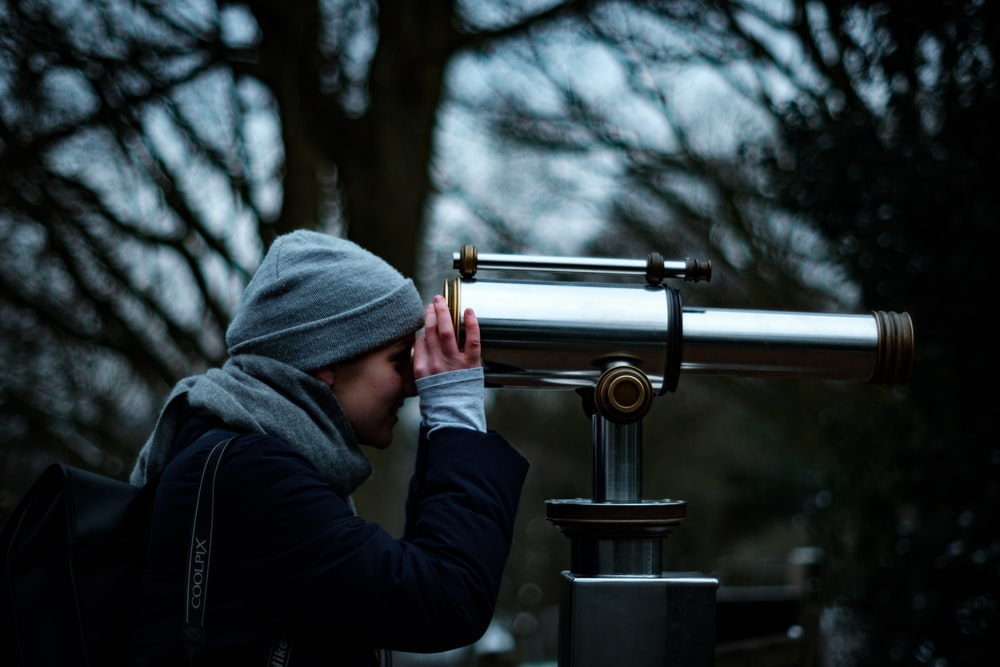 person looking at telescope under trees during daytime