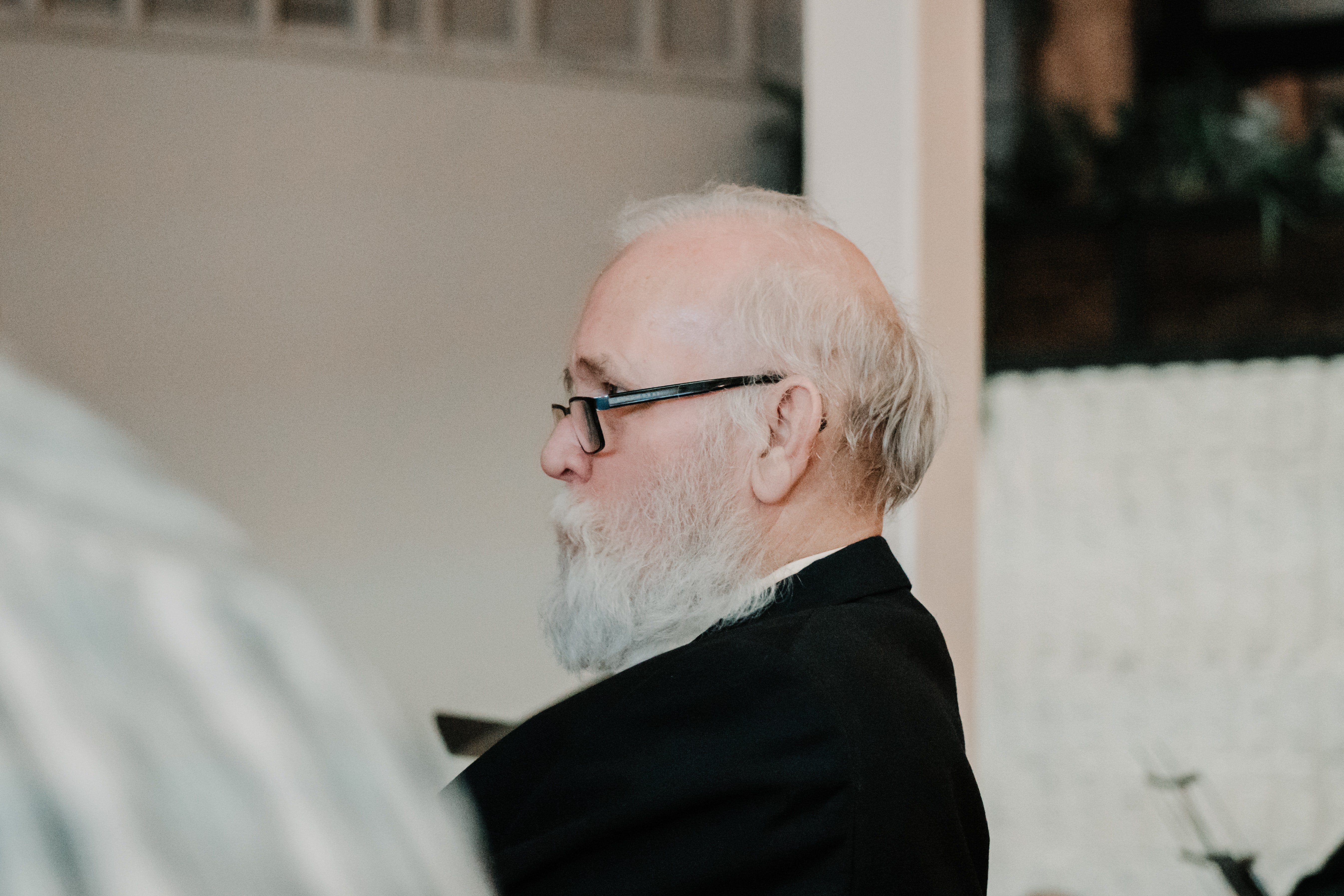 bearded man wearing eyeglasses sitting