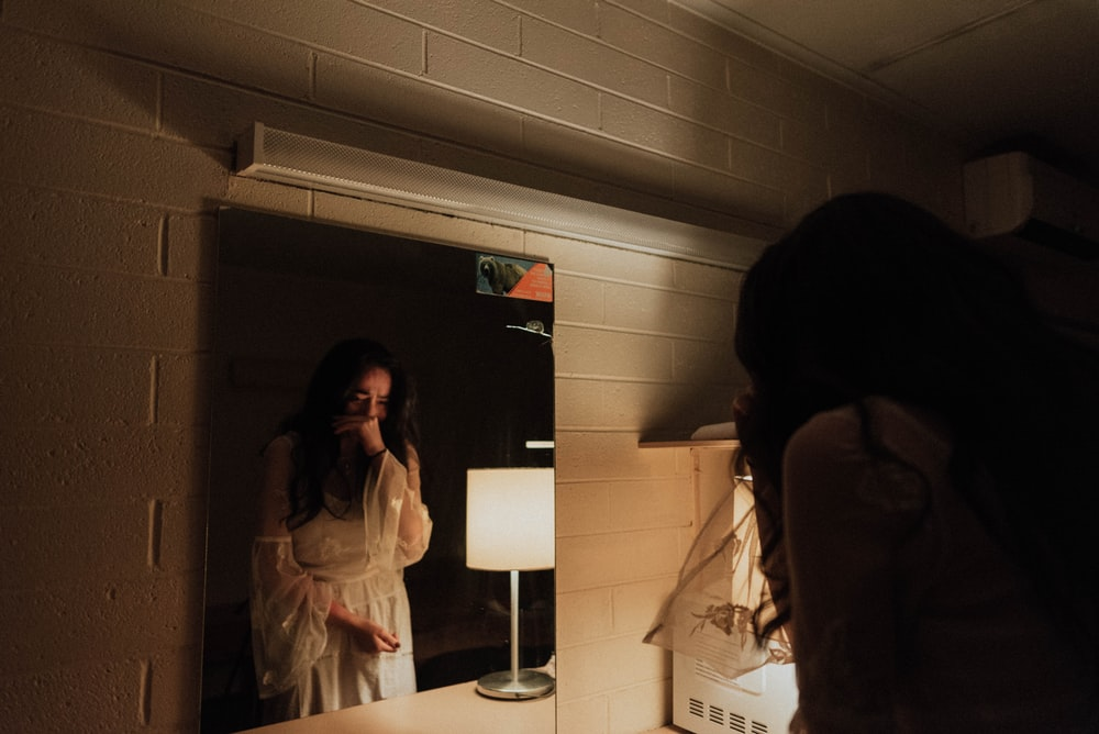 woman crying in front of mirror