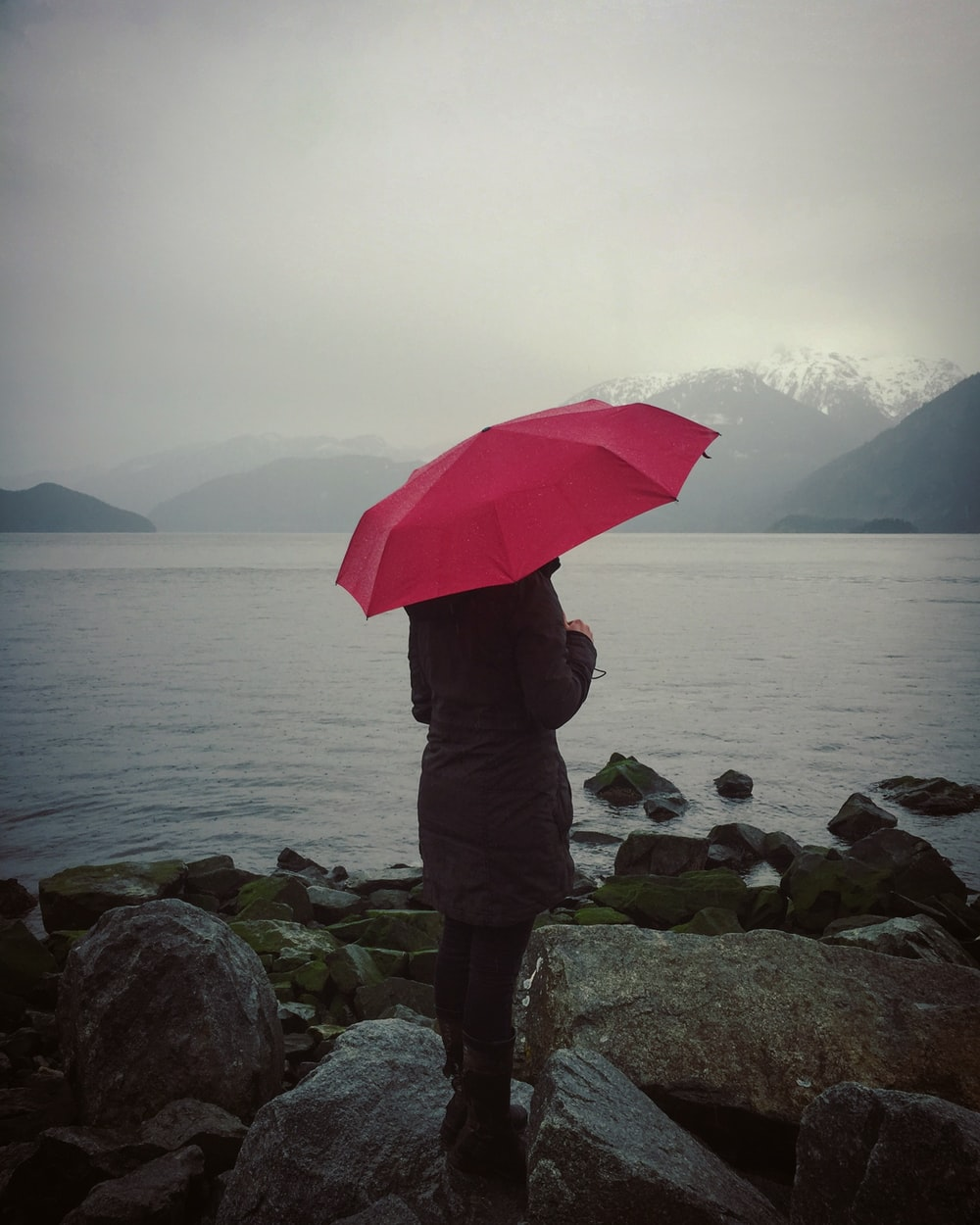 woman holding red umbrella standing on rocks