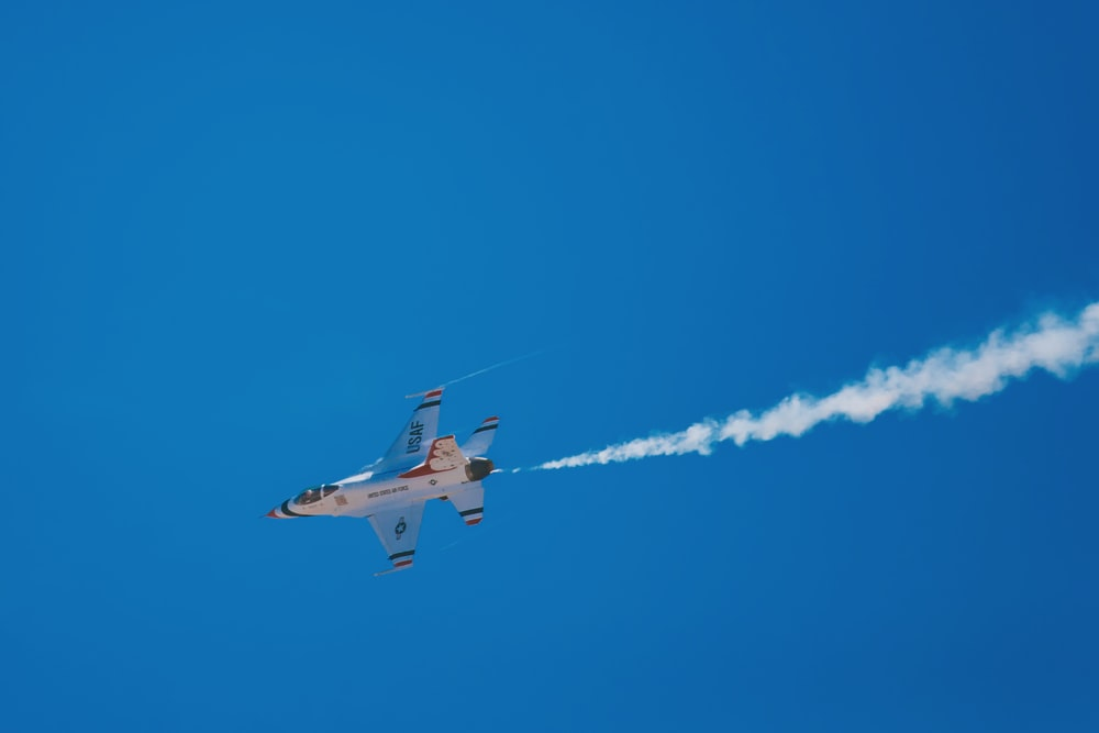 white and blue jet flying under clear blue sky