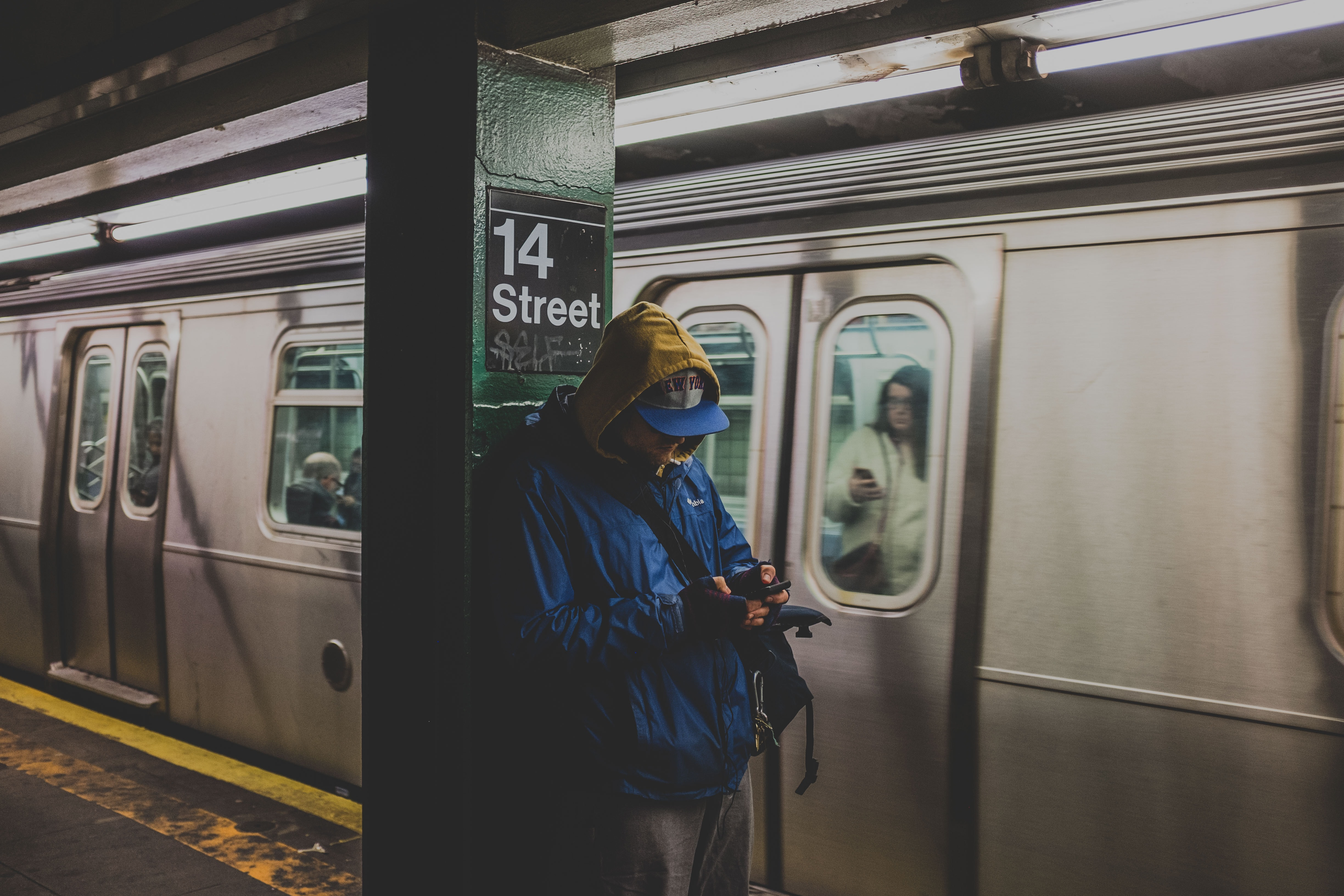 man in blue hoodie using smartphone in train station with train nearby