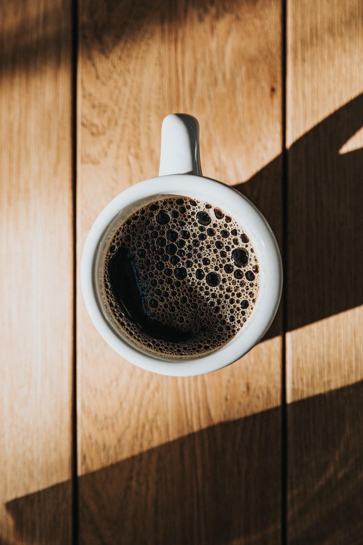 white ceramic mug on brown wooden surface