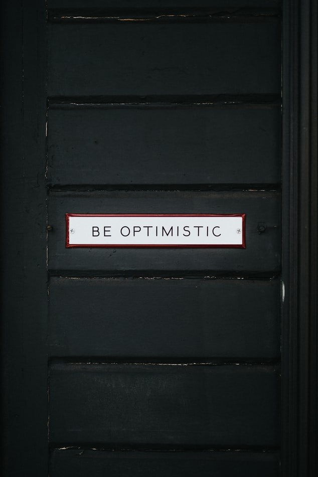 "A photo of a black door with a plaque on the front that says ""be optimistic"""