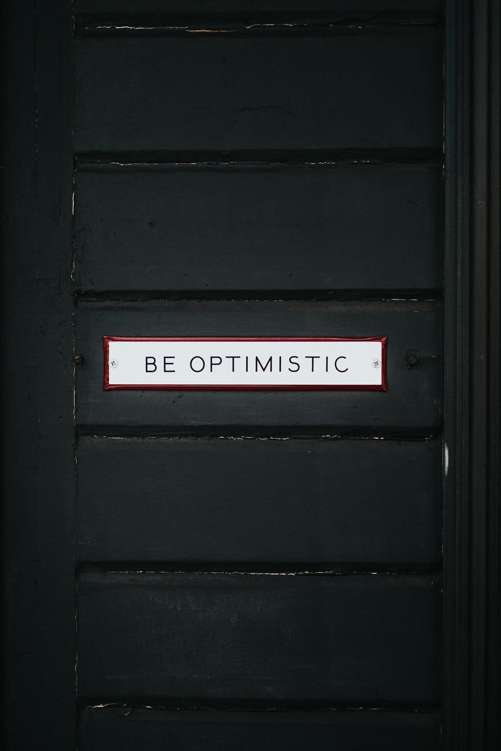 black wooden door with be optimistic text overlay