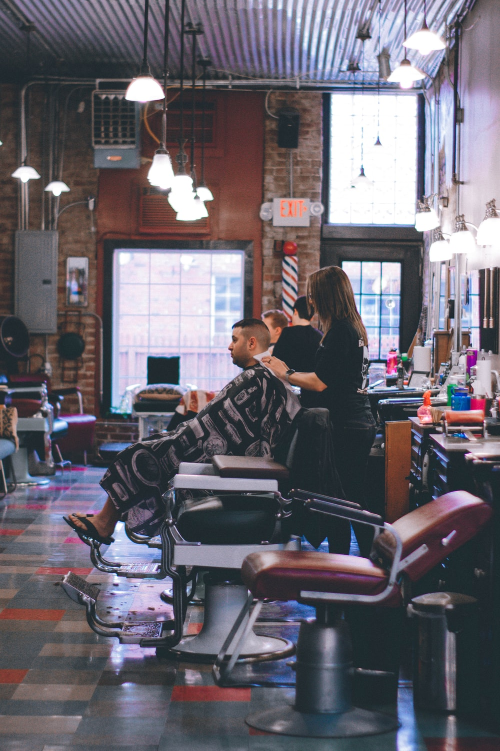 man standing beside man sitting on barber chair