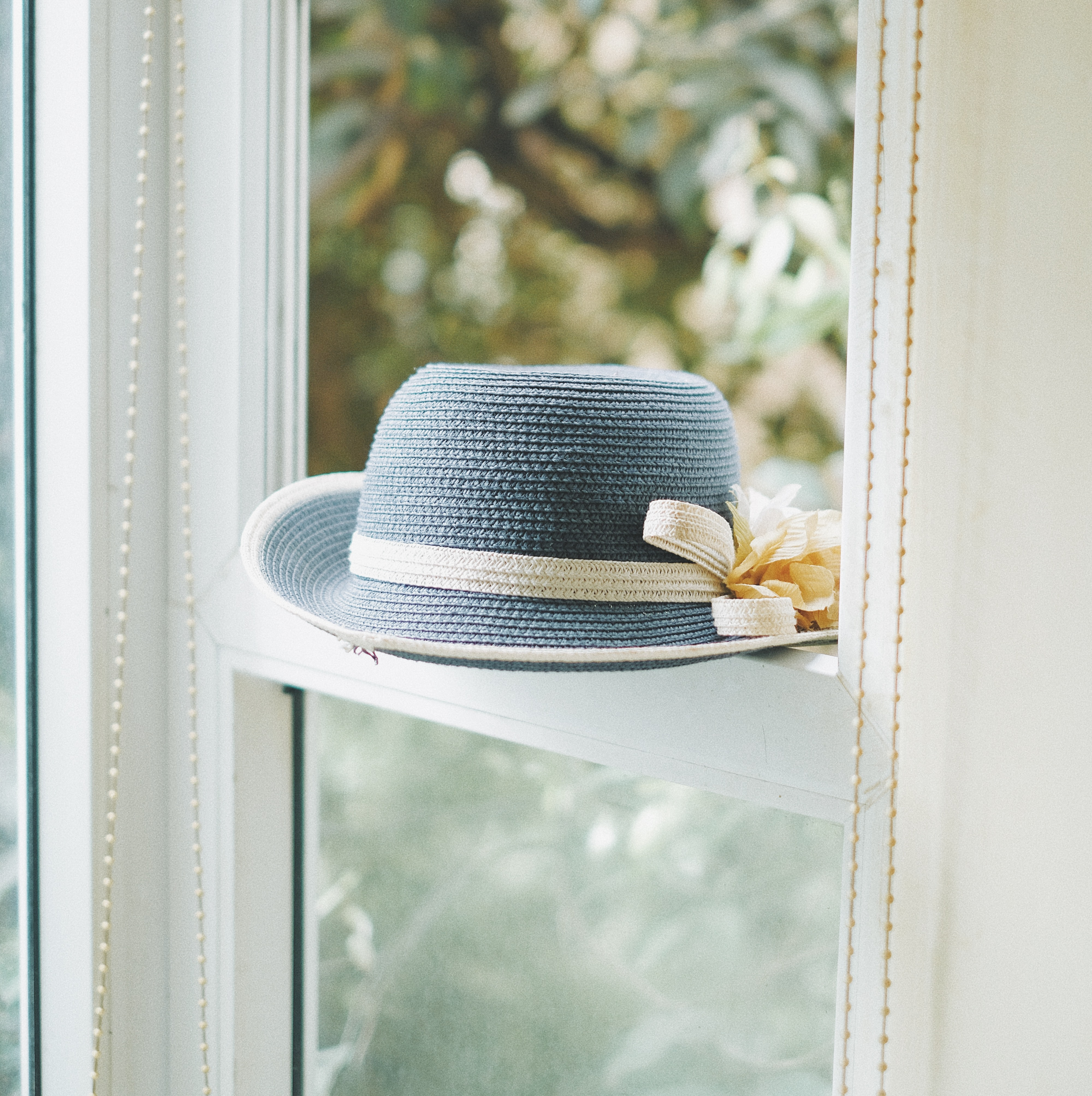 grey knitted hat on window