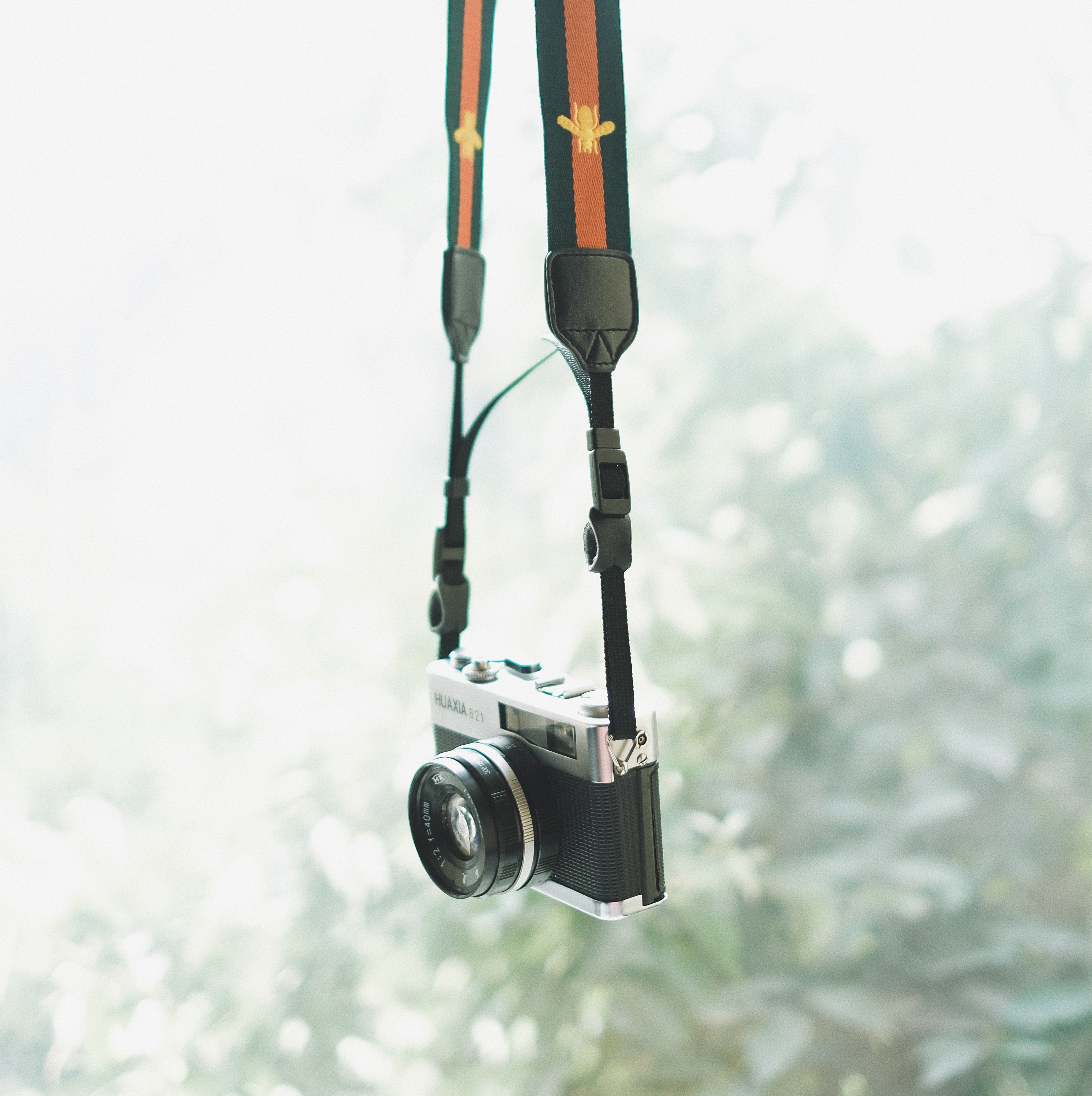 selective focus photography of hanging black and gray DSLR camera