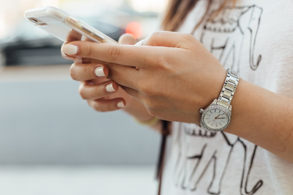 woman holding iPhone during daytime
