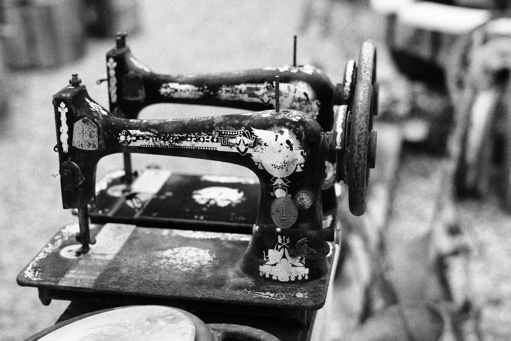 grayscale photo of two sewing machine