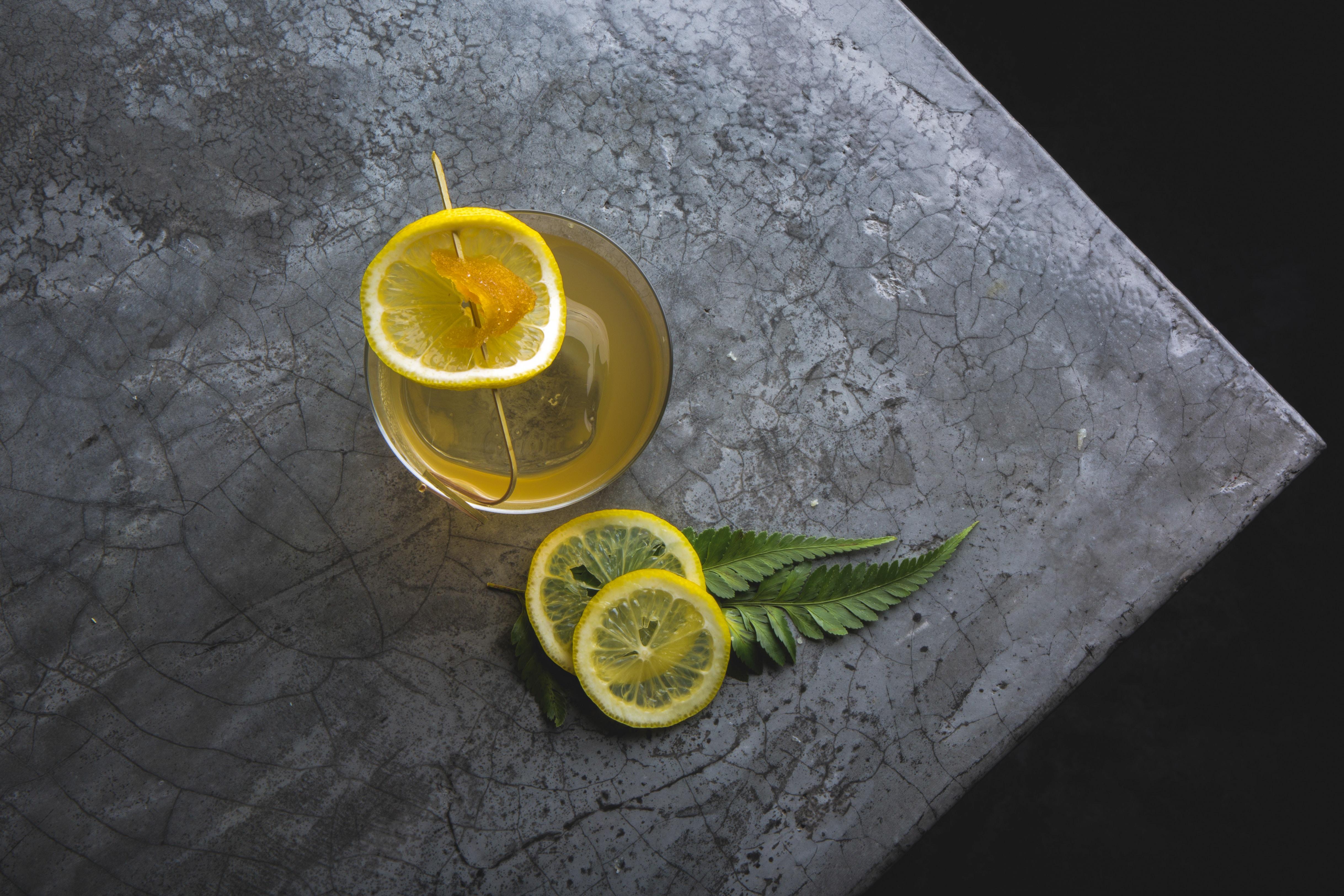 three lemon slice near glass on gray surface
