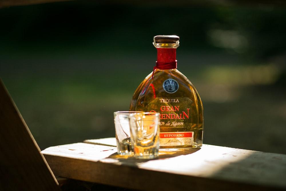 two rock glasses beside bottle