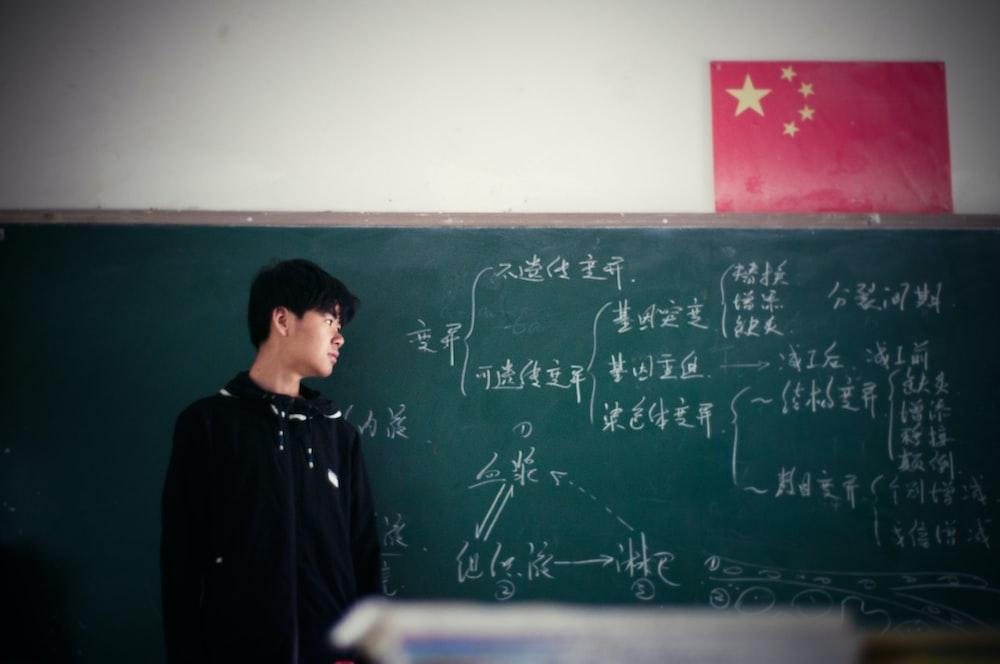 man standing in front of chalkboard inside classroom