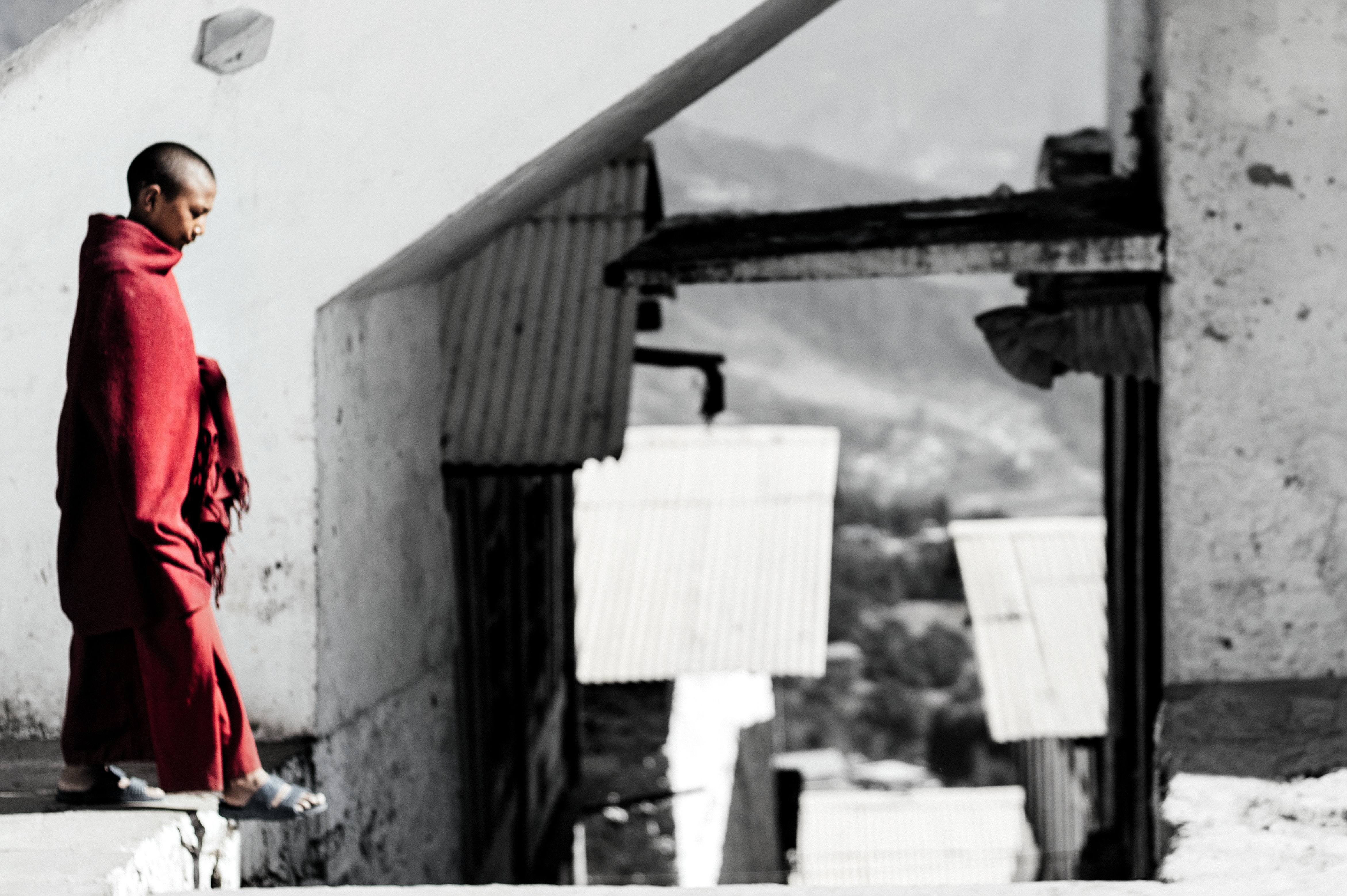 selective color photography of man standing on concrete surface