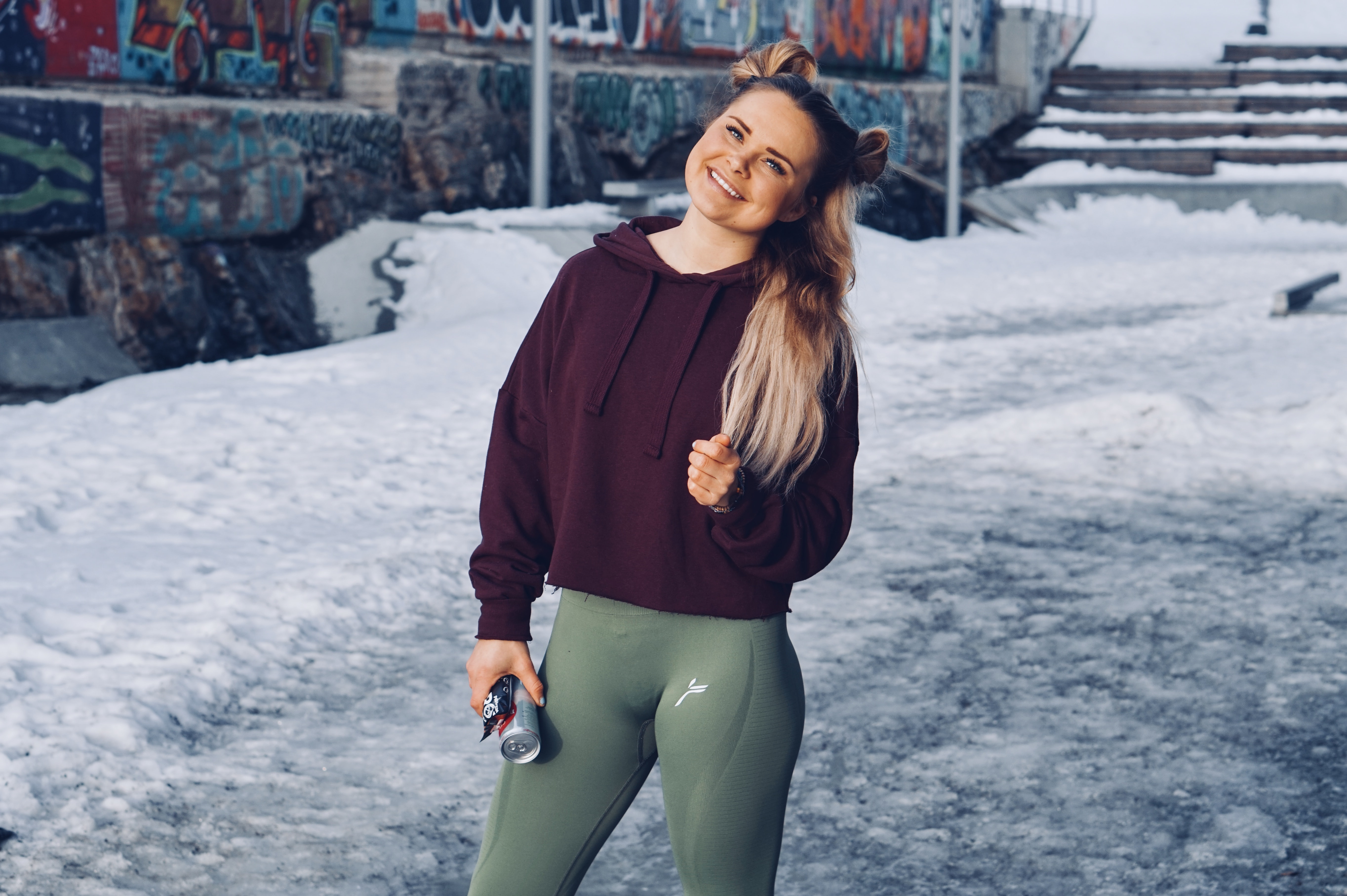 smiling woman tilting its while holding can standing on snow