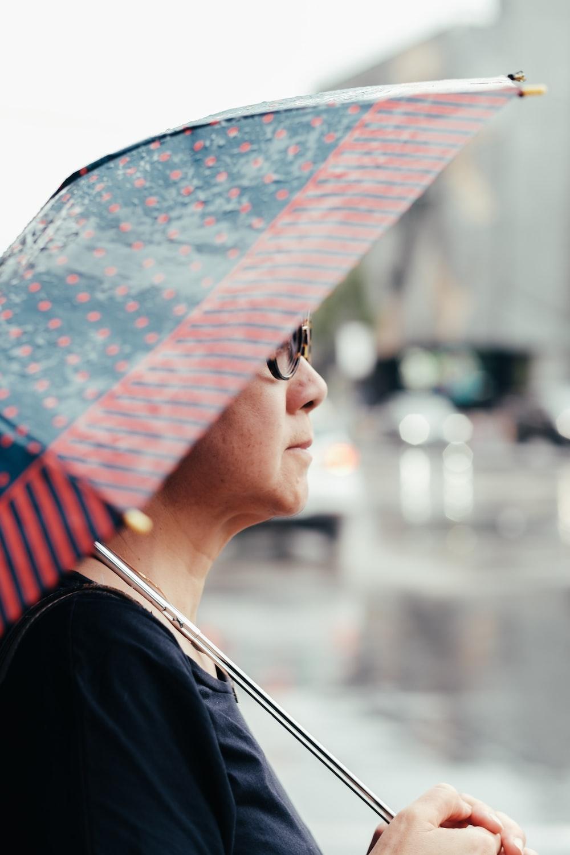 selective focus photo of woman holding umbrella