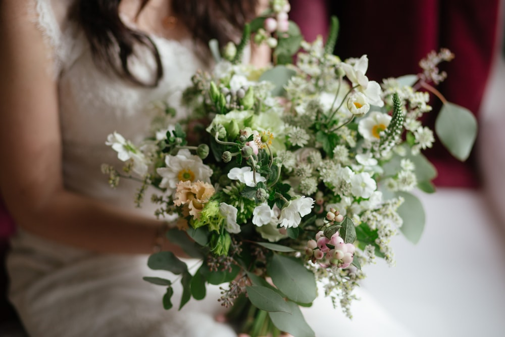 woman in white bridal holding bouquet of white flowers