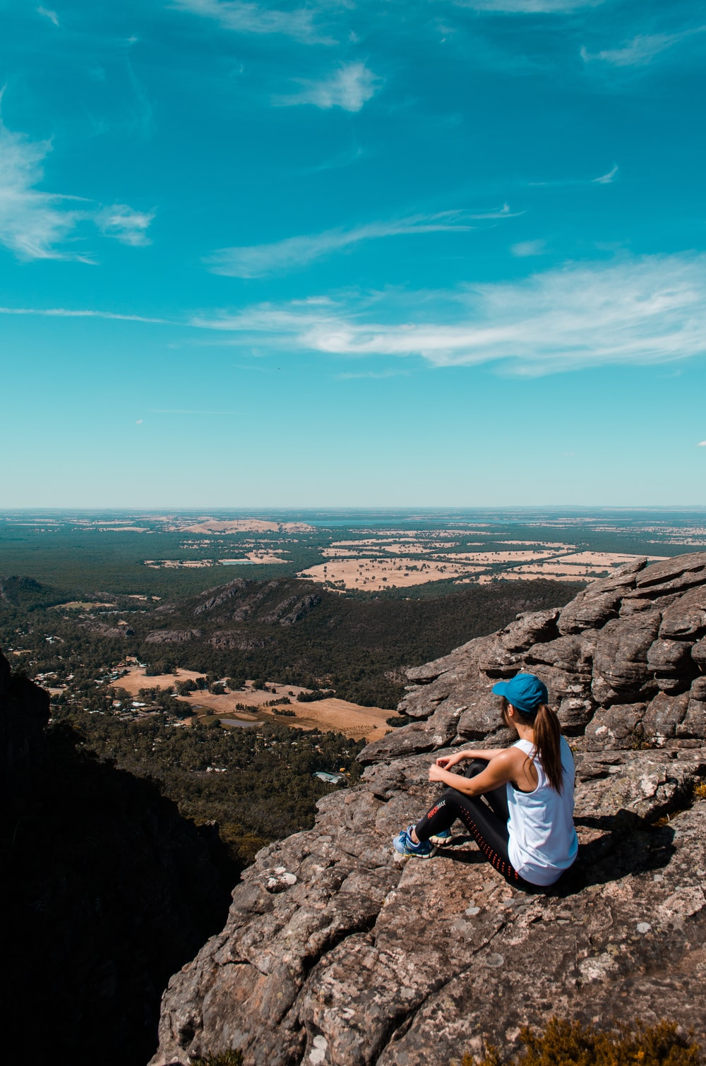 woman sitting on cliff under blue sky at daytime
