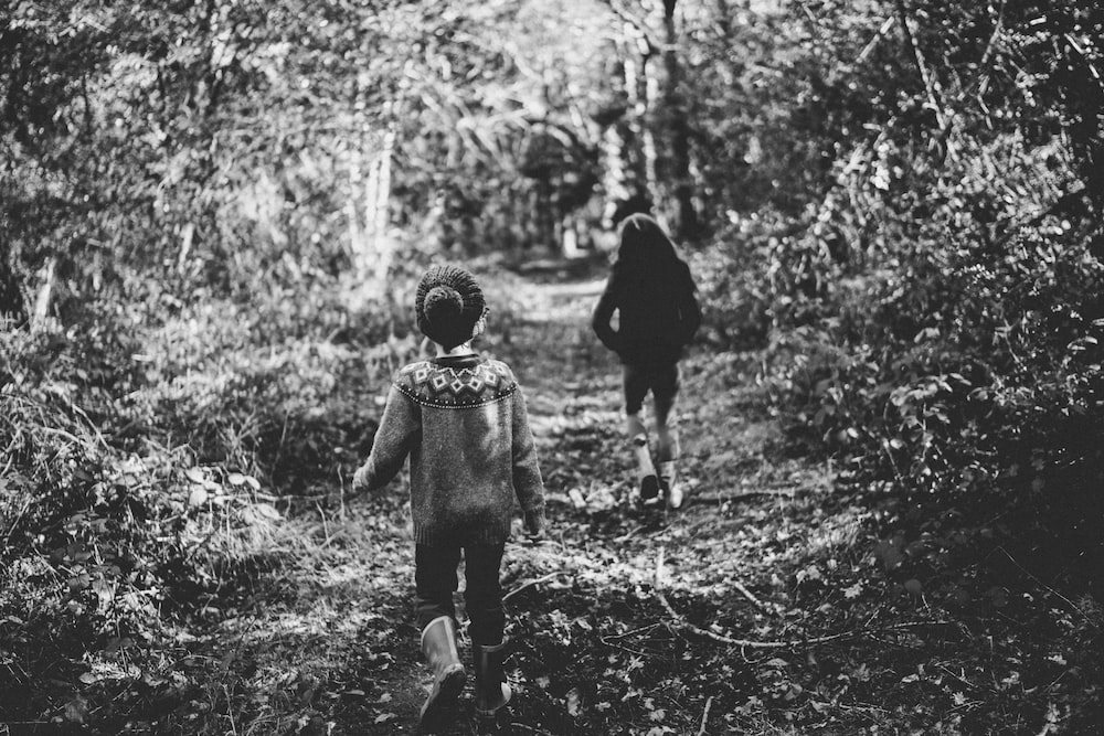 greyscale photo of two children surrounded by plants