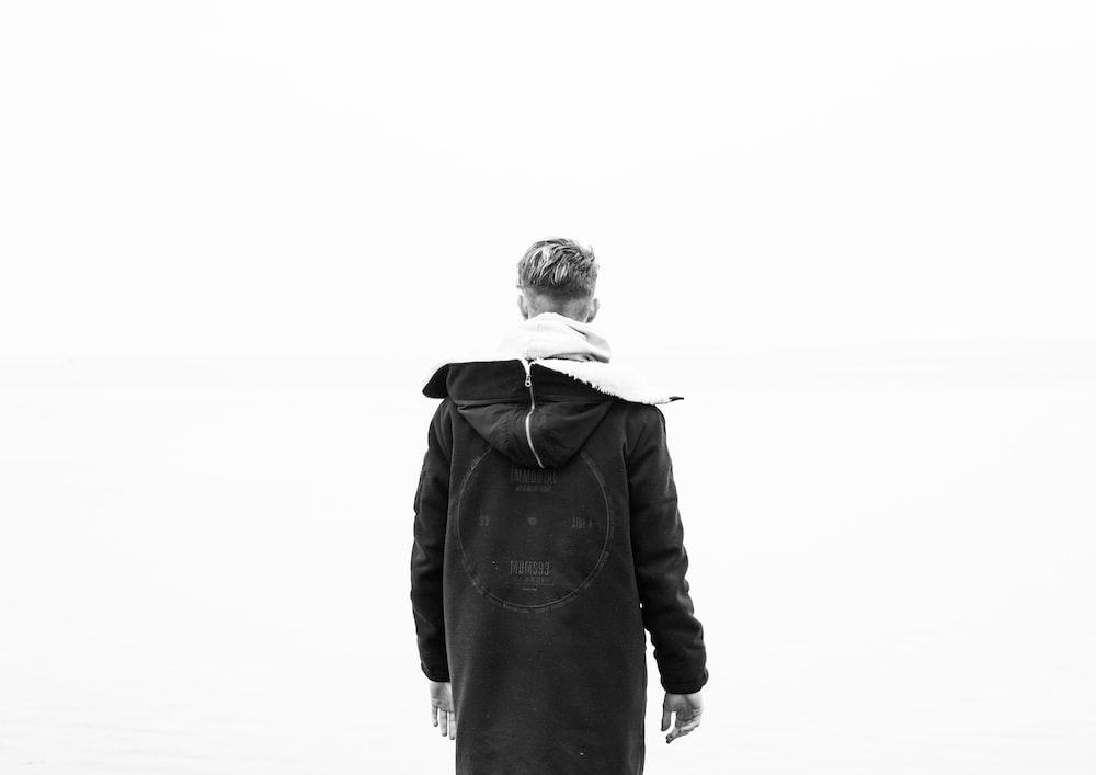 man standing wearing black overcoat hoodie