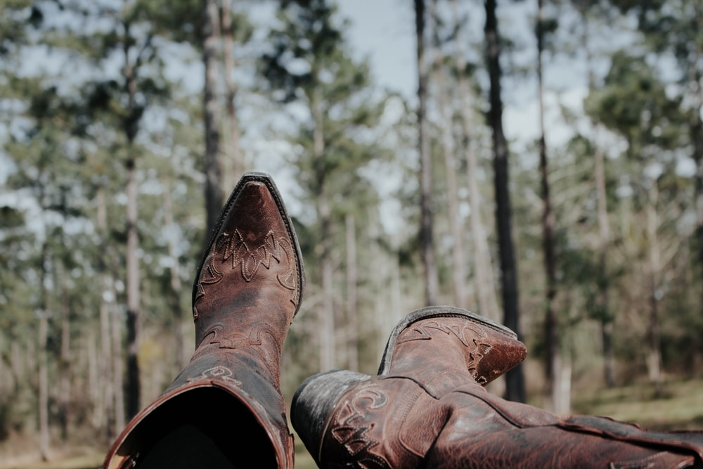 selective focus photography of person wearing cowboy boots