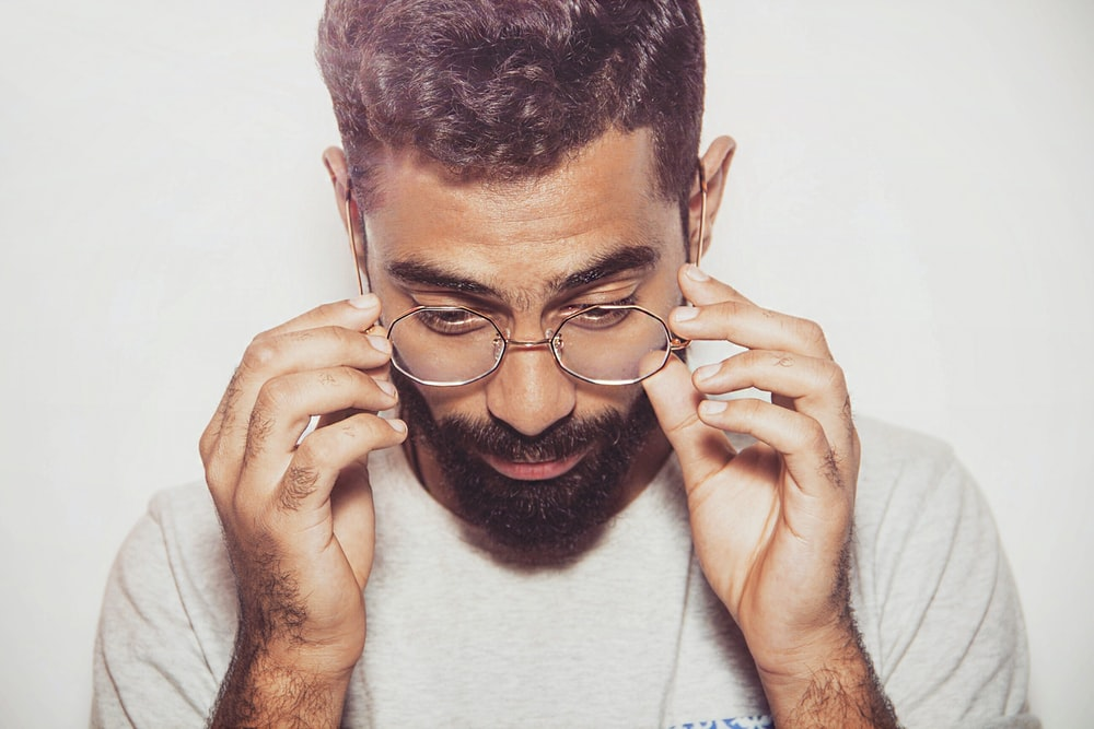 man about to hold eyeglasses