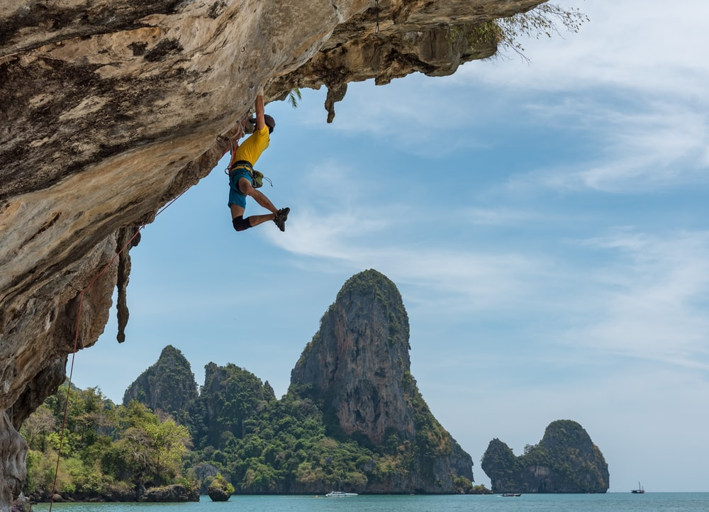 man climbing cliff beside beach