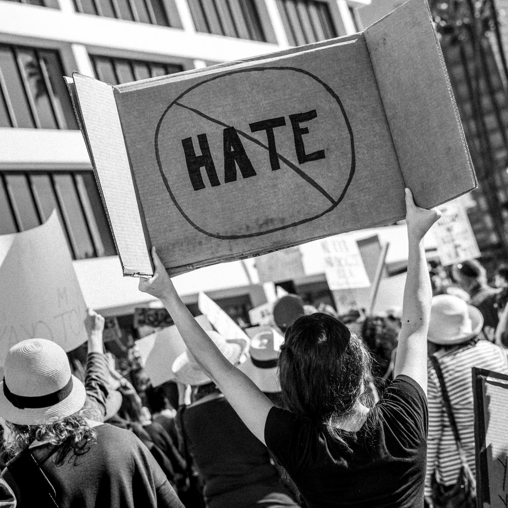 woman holding Hate signage