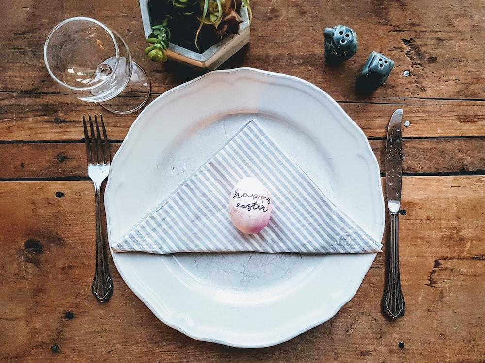 white ceramic plate beside gray fork