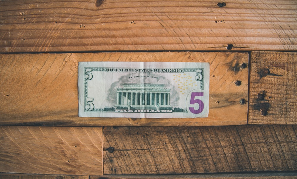 5 U.S dollar on brown wooden surface