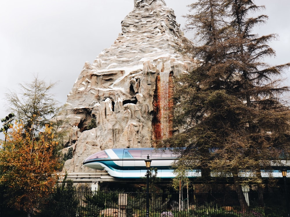 blue and white train beside brown rock mountain and pine trees