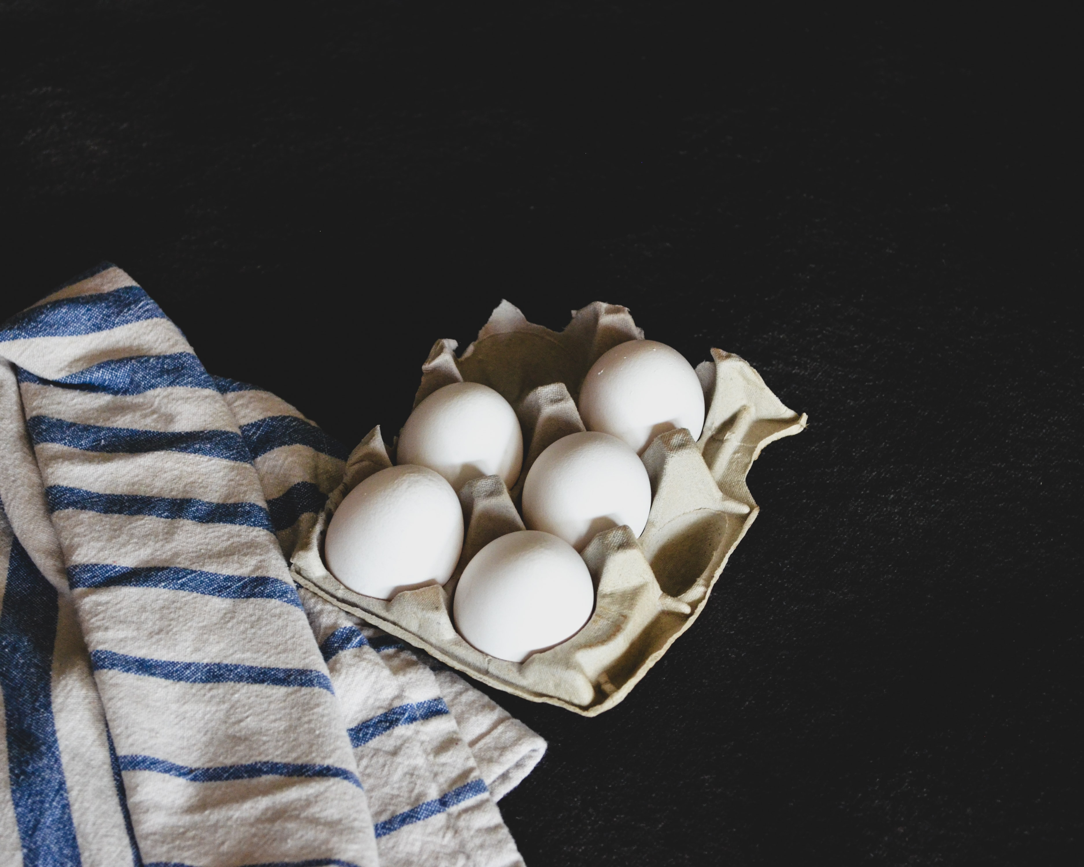 five eggs on brown carton tray