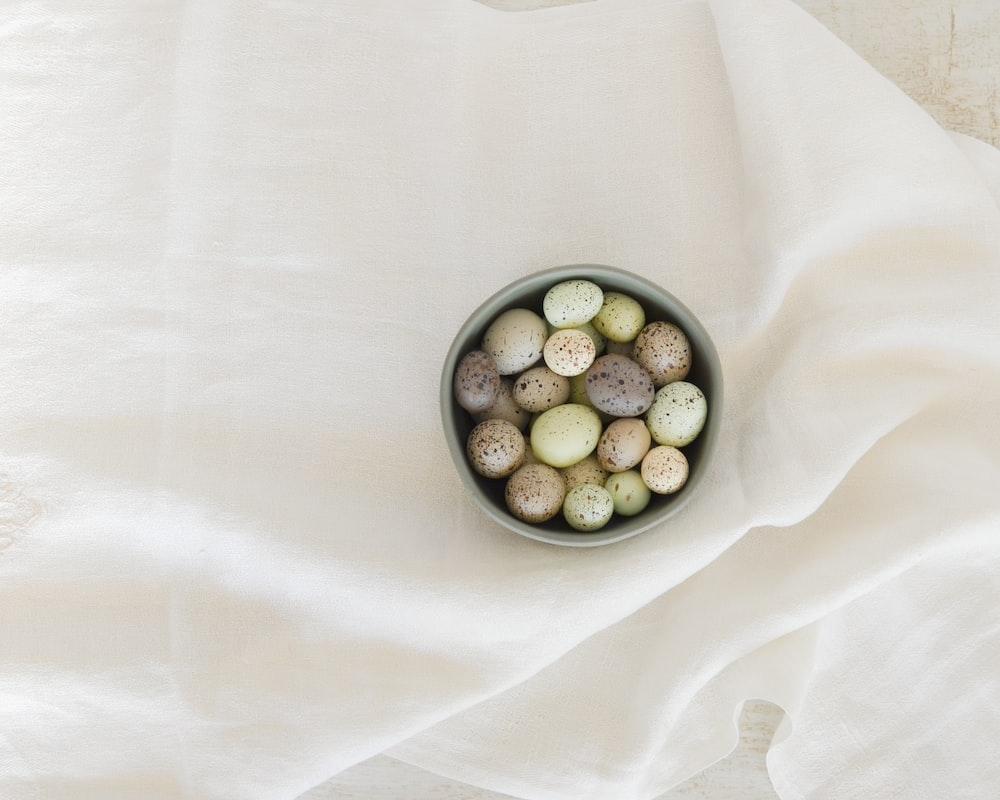 pebbles in gray ceramic bowl on white textile