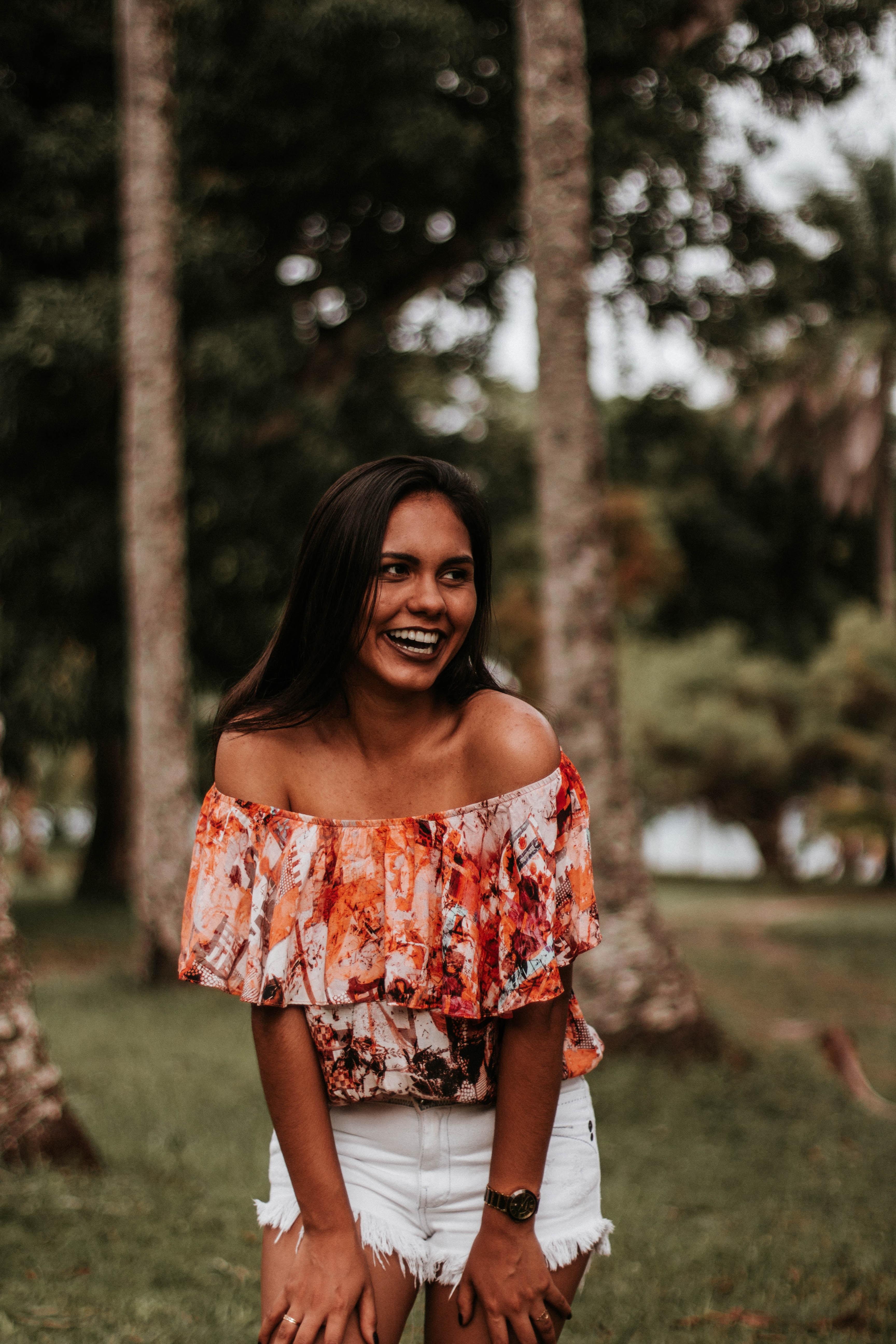 woman in orange off-shoulder dress laughing beside trees