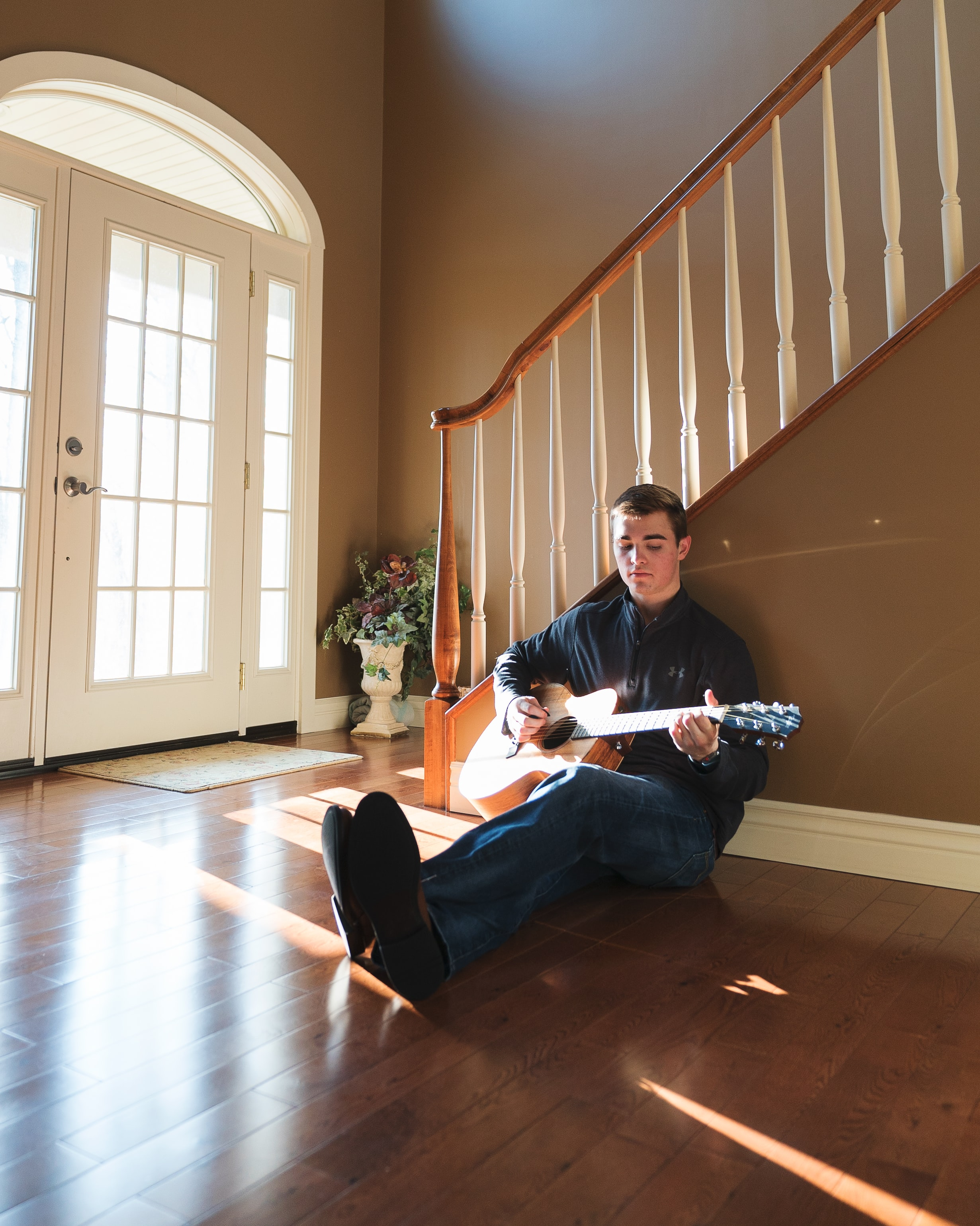 man playing guitar leaning on stairs