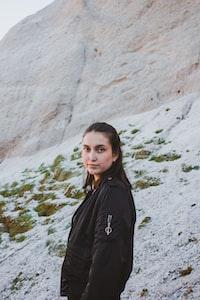 woman standing beside rock formation