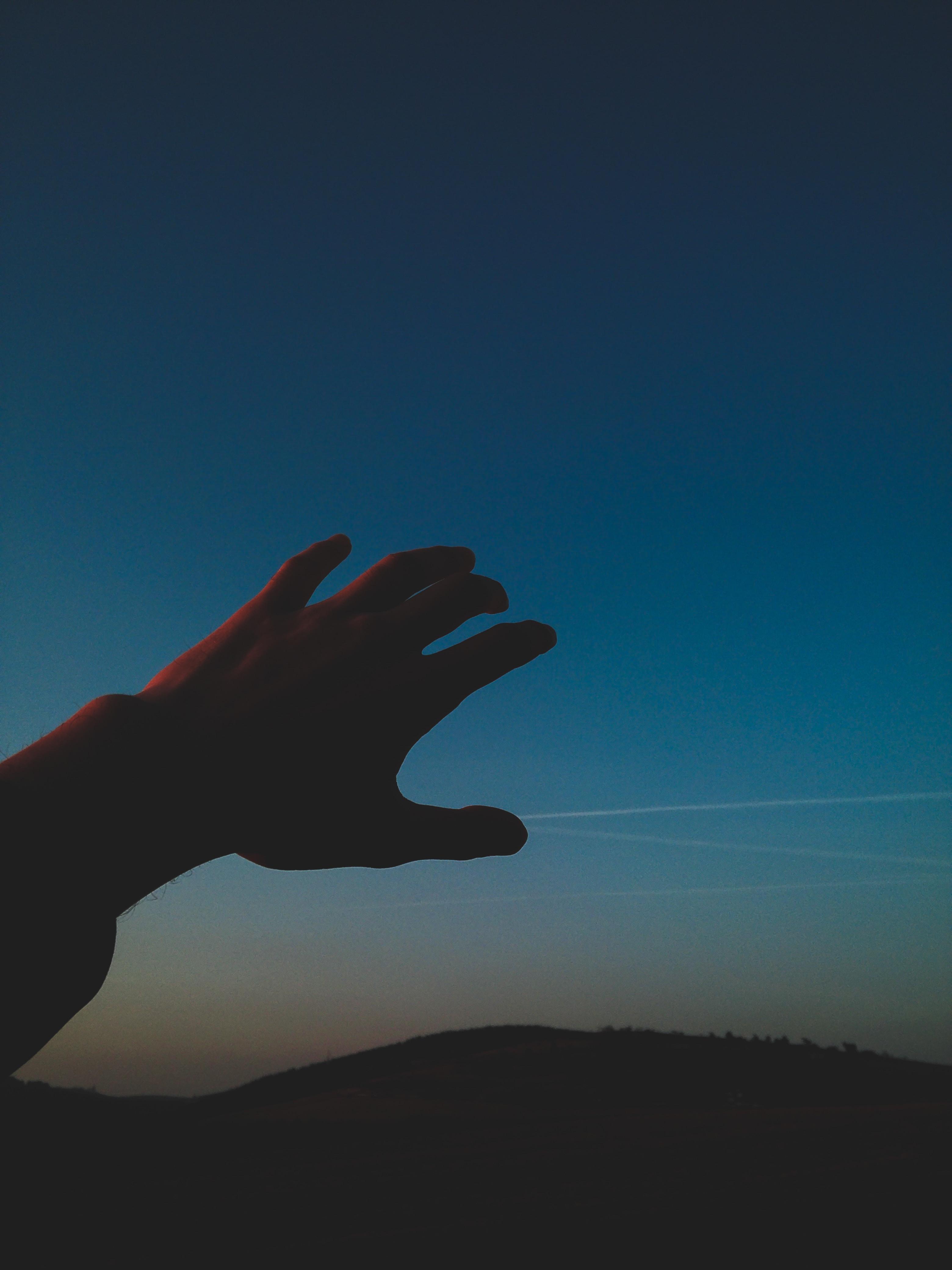 person raising hand on sky