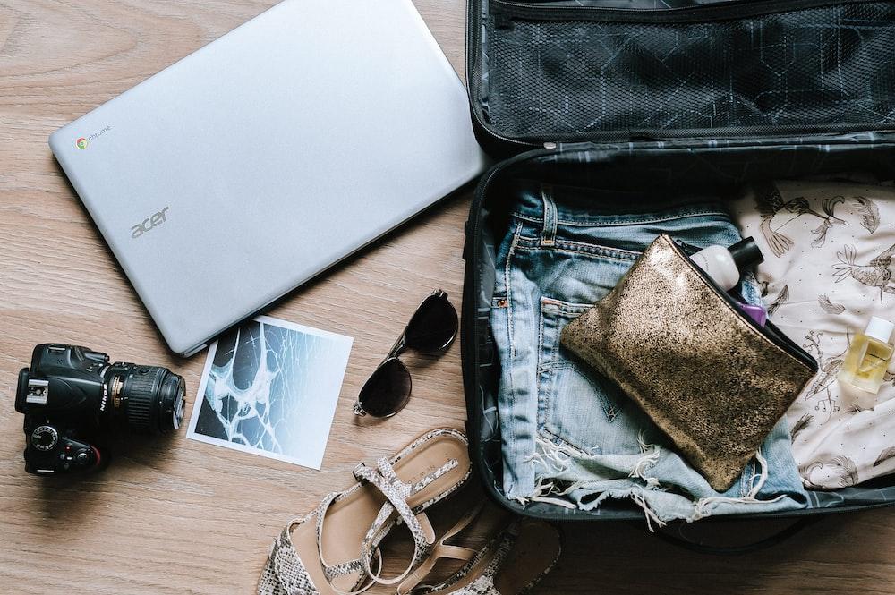 black DSLR camera near sunglasses and bag