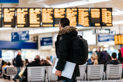 man standing inside airport looking at LED flight schedule bulletin board