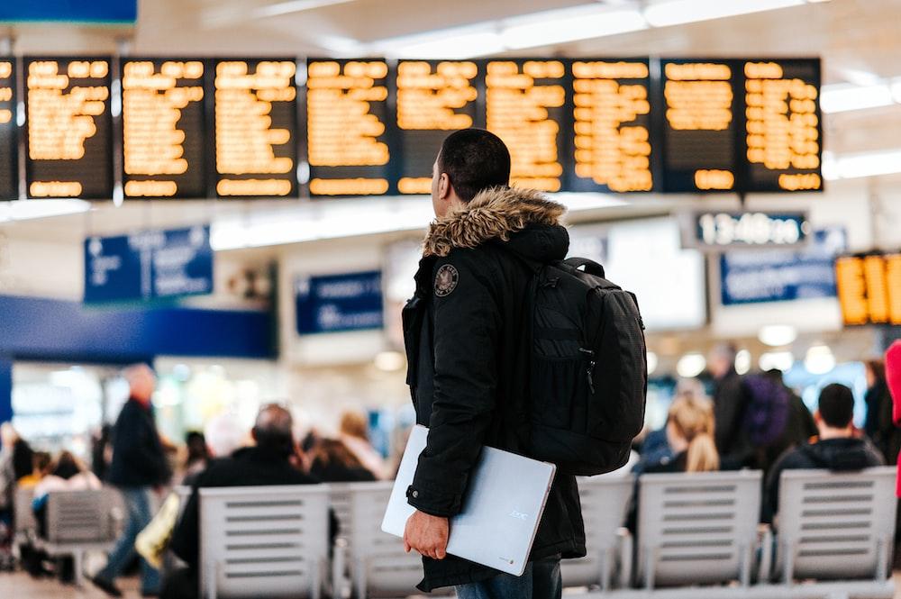 LEDフライトスケジュール掲示板を見て空港の中に立っている人