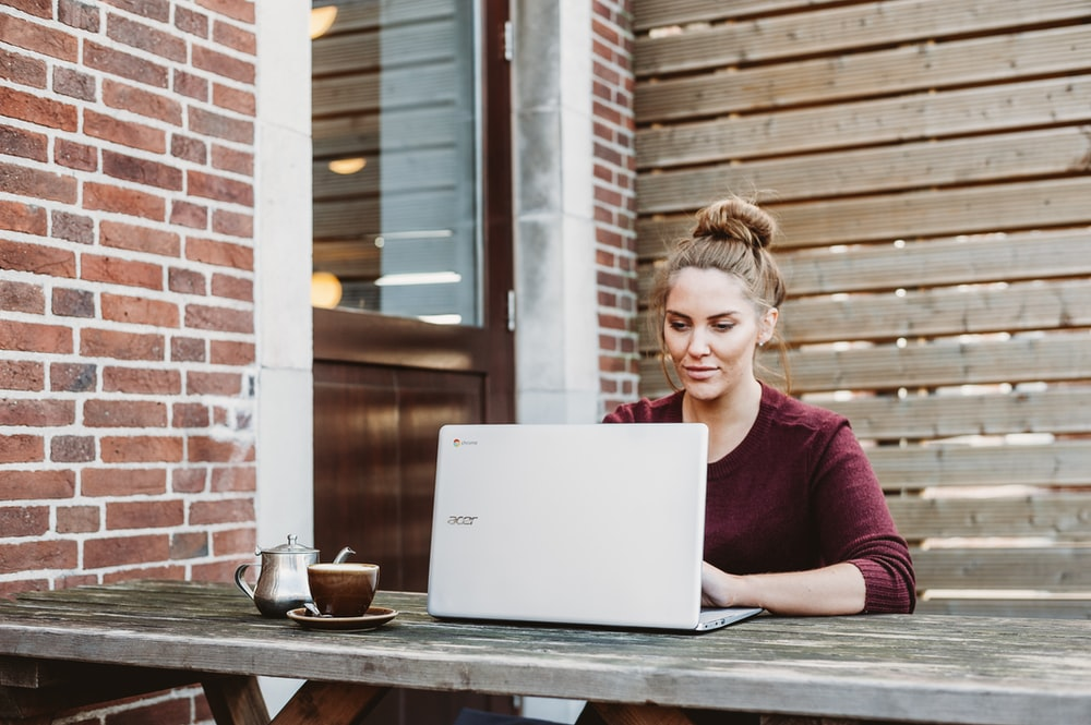 woman sitting and holding white Acer laptop near brown wooden wall