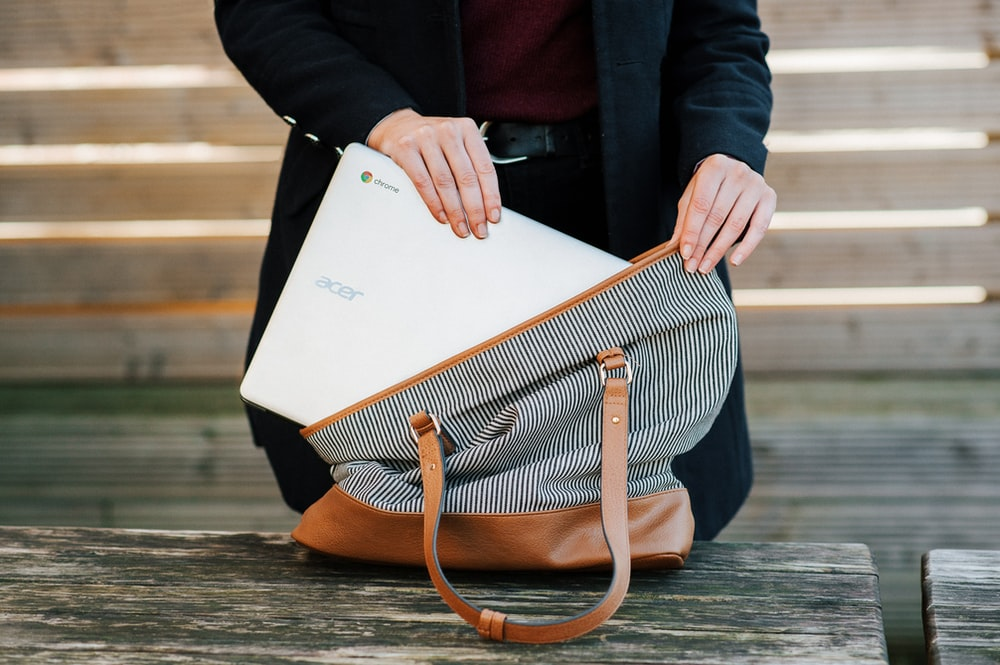 woman putting an Acer Chromebook in a bag