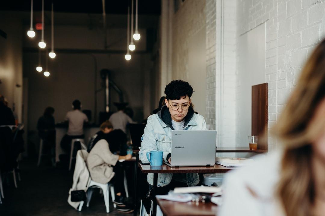woman wearing white jacket using laptop computer