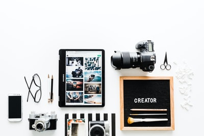 flat view of cameras beside computer tablet and smartphone creative teams background