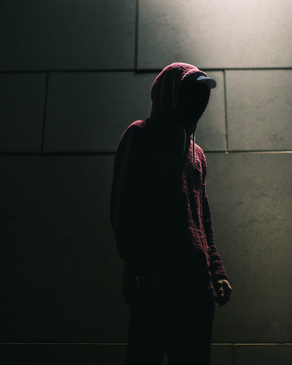 person in red hoodie standing in front of gray brick wall