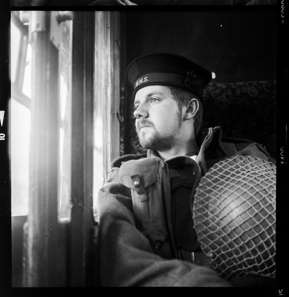 man sitting on bench holding vintage helmet