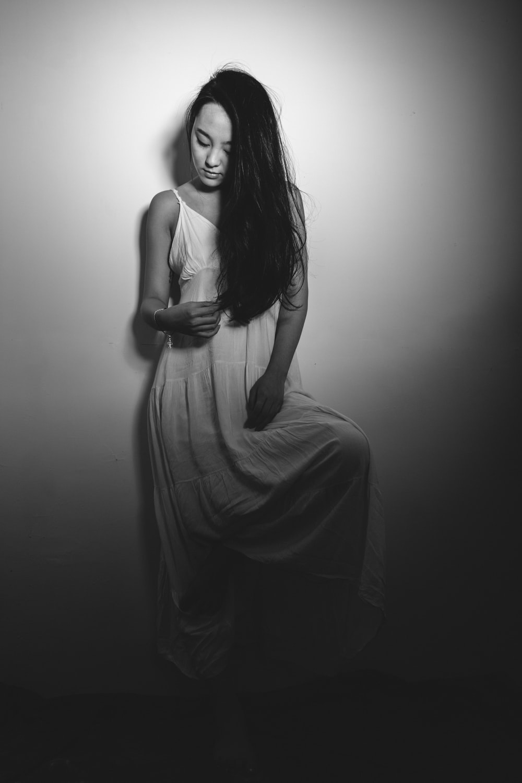 woman wearing spaghetti strap maxi dress leaning on wall