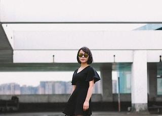 woman in black minidress and black sunglasses standing on street